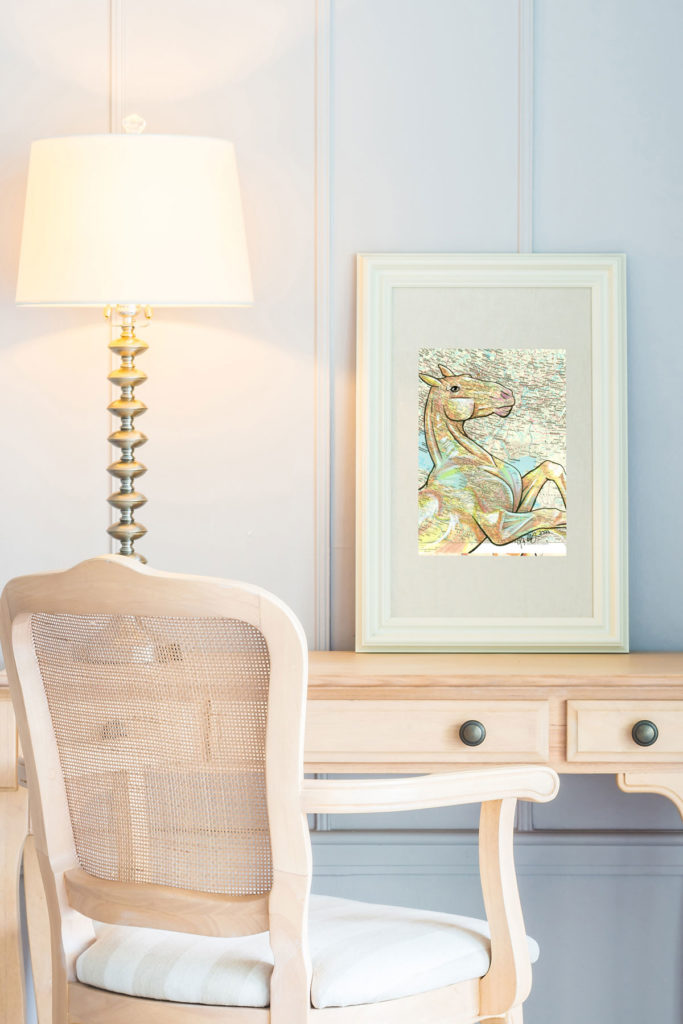Image of a room with a white desk and chair in front of a white wall. A lamp is on the desk. A framed image of a drawing of an Akhal-teke horse is on the desk
